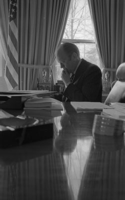 March 25, 1975 – The White House – Oval Office – Gerald R. Ford – at desk, hand on chin; reflected in glass on desk